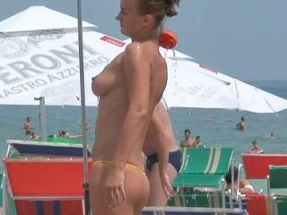 The beautiful topless bikini chick is on the beach washing out sand from the tan body