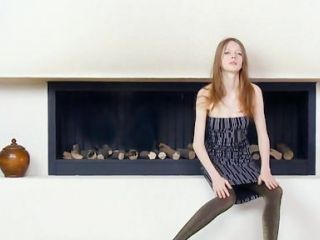Ultra skinny teen by the fireplace